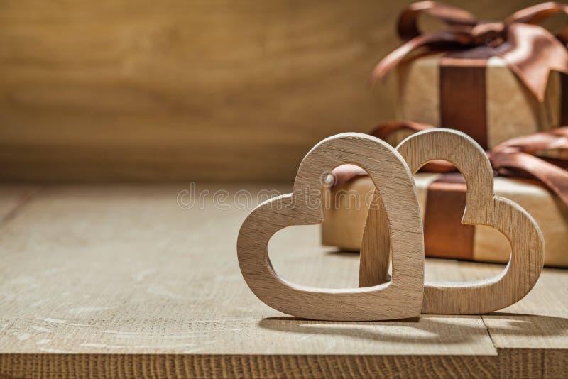 Los corazones y las cajas de regalo de madera se cierran encima de fondo de madera fotografía de archivo