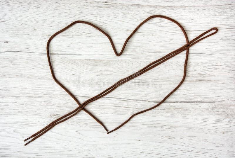 Los cordones de Brown formaron en el corazón en el fondo de madera, Va fotos de archivo libres de regalías
