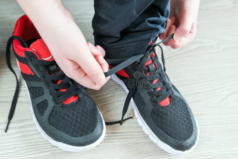Los cordones de zapatillas deportivas del muchacho foto de archivo