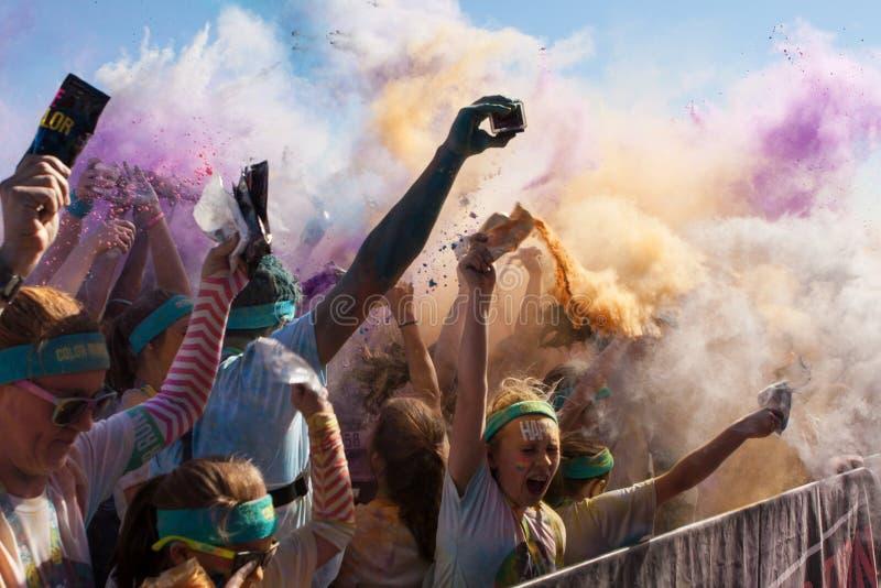 Los corredores crean la explosión del color con los paquetes de almidón de maíz coloreado foto de archivo libre de regalías