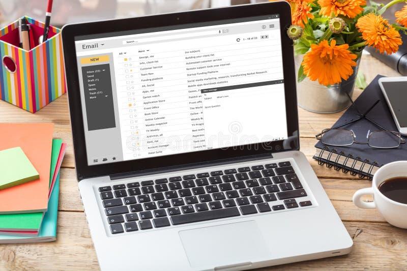 Los correos electrónicos enumeran en una pantalla del ordenador portátil en un escritorio de oficina fotografía de archivo