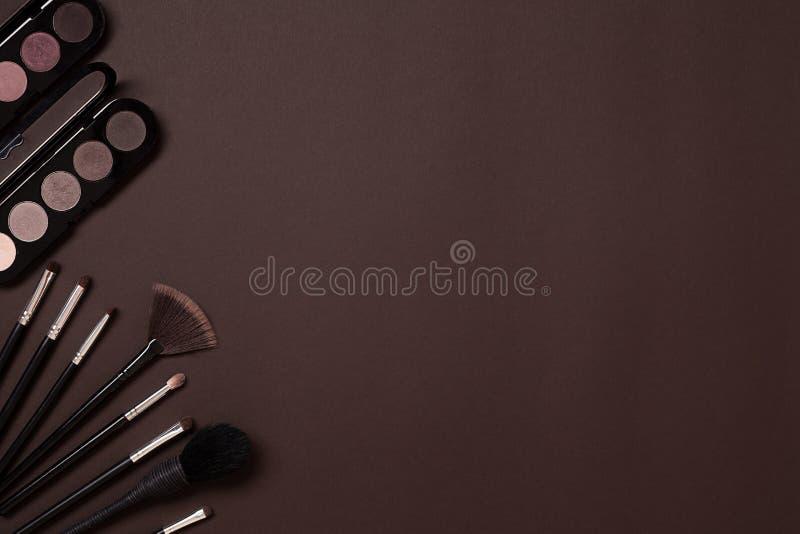 Los cosméticos del ` s de las mujeres fijaron en un fondo marrón, mujer moderna imagen de archivo
