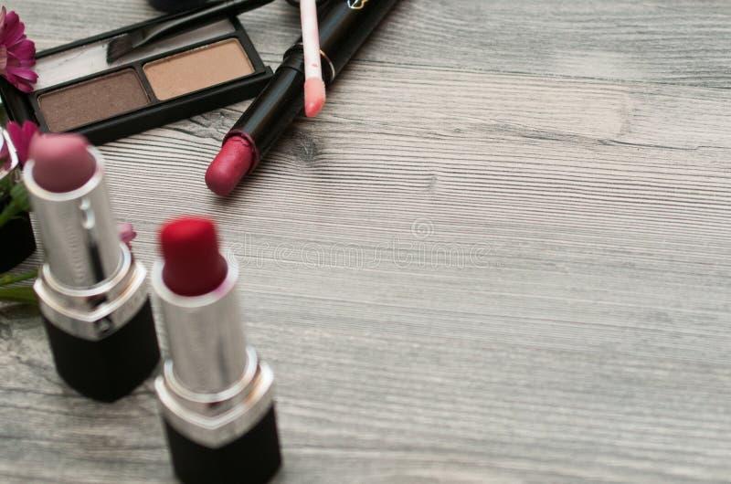Los cosméticos modelan con componen objetos del artista: lápiz labial, clavo, perfumes, rimel Fondo de la belleza fotos de archivo libres de regalías
