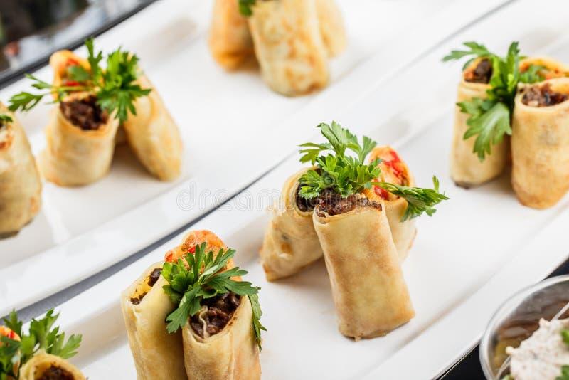 Los crespones rellenos remataron con la carne y las verduras en placa en la tabla de banquete Cierre de la comida gastrónoma para fotos de archivo