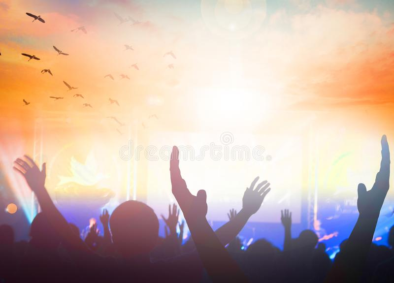 Los creyentes devotos aumentan sus manos en la adoración fotografía de archivo