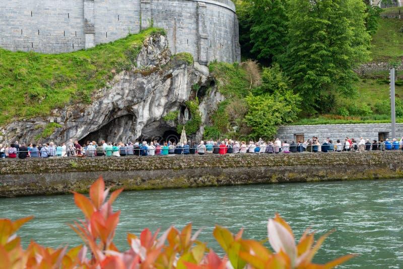 Los creyentes y los turistas acercan a la gruta en Lourdes La gruta es capilla católica a nuestra señora en Lourdes fotografía de archivo libre de regalías