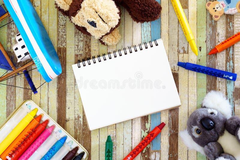 Los creyones, juguetes, las muñecas lindas con el espacio en blanco abren el cuaderno y el creyón o imagen de archivo