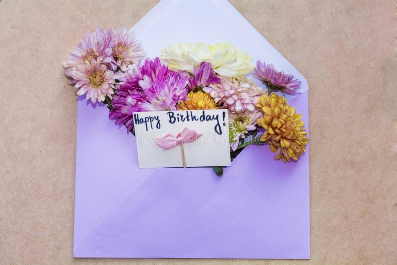 Los crisantemos florecen en el sobre violeta con la tarjeta del feliz cumpleaños de i imágenes de archivo libres de regalías