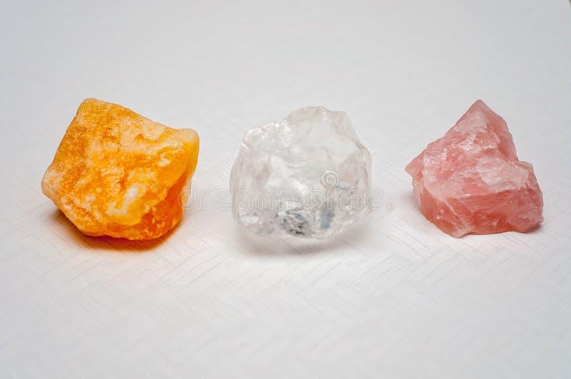 Los cristales curativos traen buenos ambientes y vibraciones positivas: cuarzo claro, calcita y cuarzo color de rosa imágenes de archivo libres de regalías