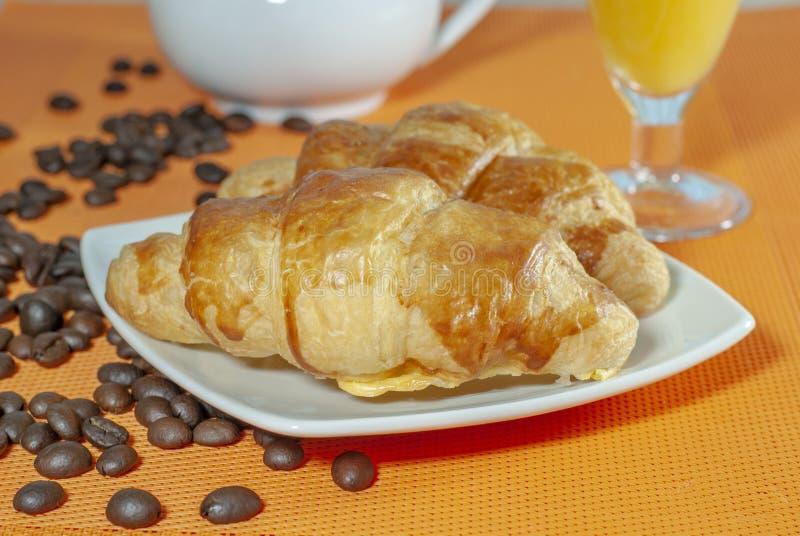 Los cruasanes con mantequilla y el melocotón atascan con café y juic anaranjado foto de archivo libre de regalías