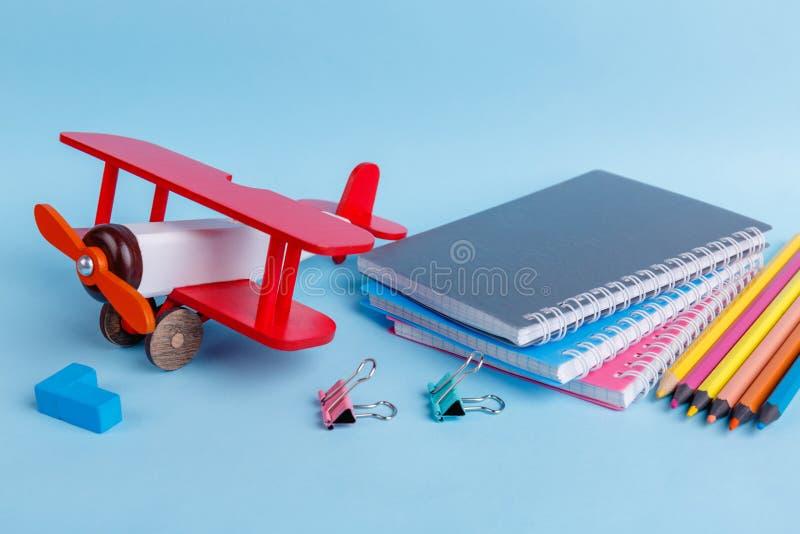 Los cuadernos, clips, colorearon los lápices, tiza y un aeroplano de madera del juguete está situado en un fondo azul foto de archivo