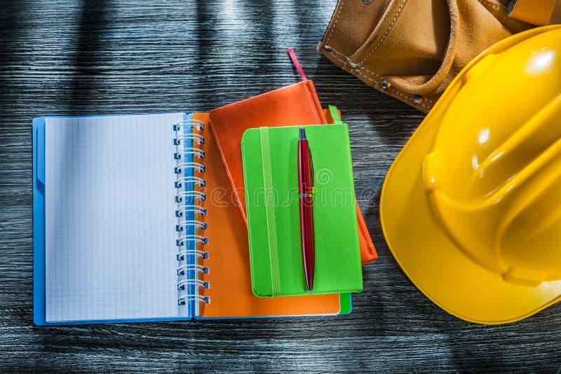 Los cuadernos encierran la correa de cuero de la herramienta de la tapa protectora en el tablero de madera fotografía de archivo