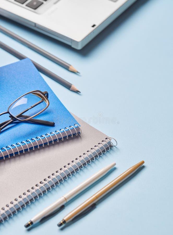 Los cuadernos, los lápices, las plumas, los vidrios y el ordenador están en la tabla imagenes de archivo