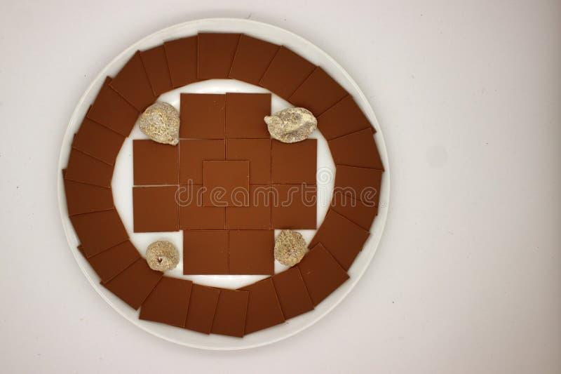 Los cuadrados del chocolate fino se presentan en un círculo y una cruz foto de archivo