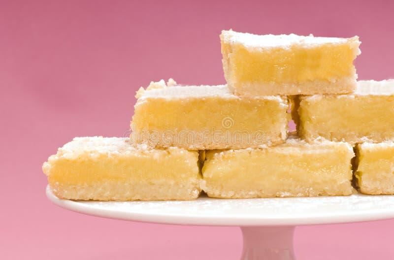 Los cuadrados recientemente cocidos al horno del limón en una torta blanca se colocan imagenes de archivo