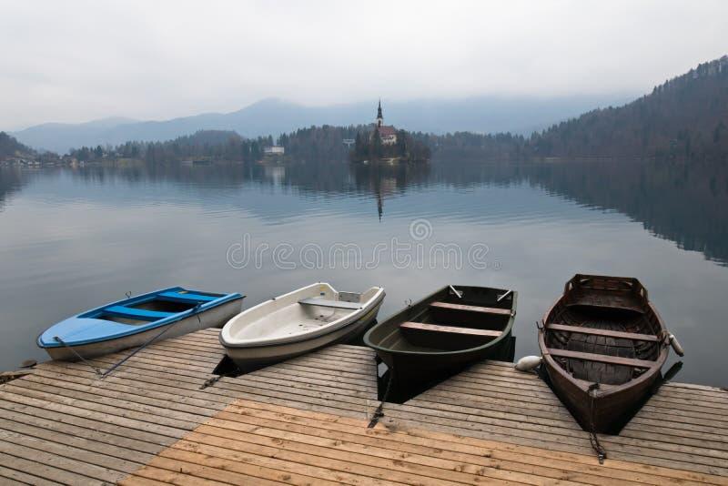 Los cuatro barcos de rowing de madera coloridos en la isla escénica maravillosa con la iglesia en el lago puro sangraron imagen de archivo