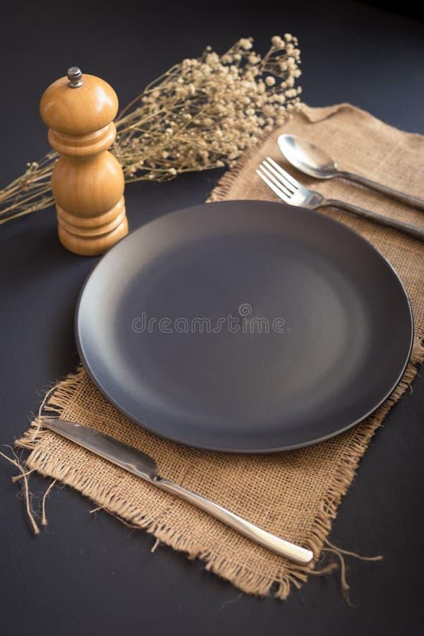 Los cubiertos negros fijaron - el cuchillo, cuchara, bifurcación, en la placa negra en sackcl foto de archivo libre de regalías