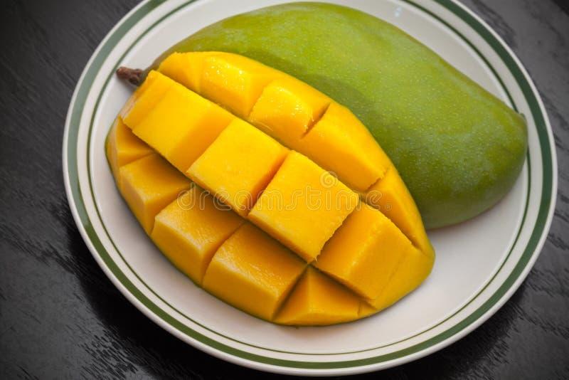 Los cubos amarillos cortaron el mango en la placa foto de archivo