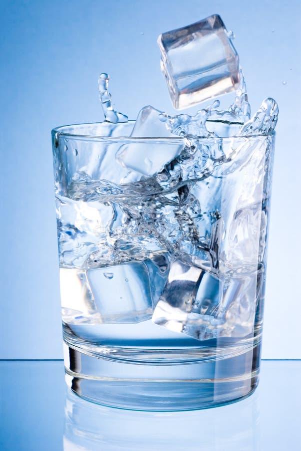 Los cubos de hielo caen en el vidrio de agua en fondo azul fotos de archivo
