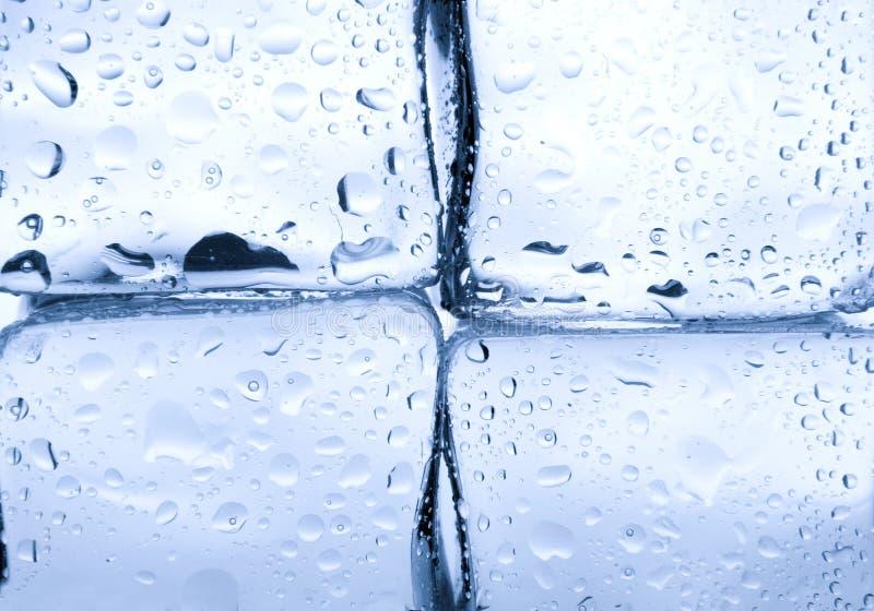 Los cubos de hielo con agua caen el fondo imagenes de archivo