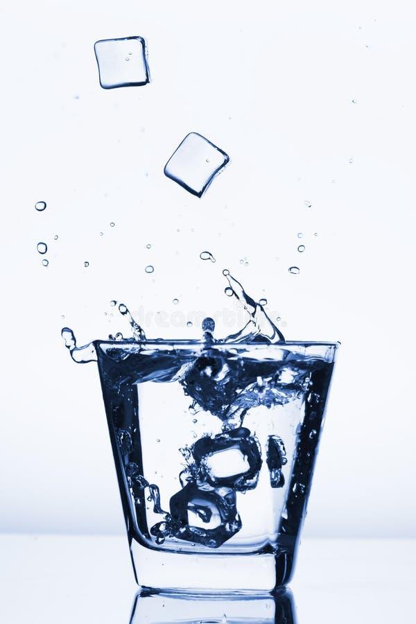 Los cubos de hielo que salpicaban en el vidrio, cubo de hielo cayeron en el vidrio de agua, agua fresca, fría, aislada en el bl a fotos de archivo libres de regalías