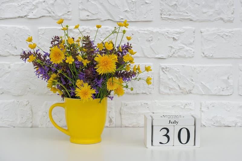 Los cubos de madera hacen calendarios el 30 de julio y la taza amarilla con las flores coloreadas brillantes contra la pared de l fotos de archivo