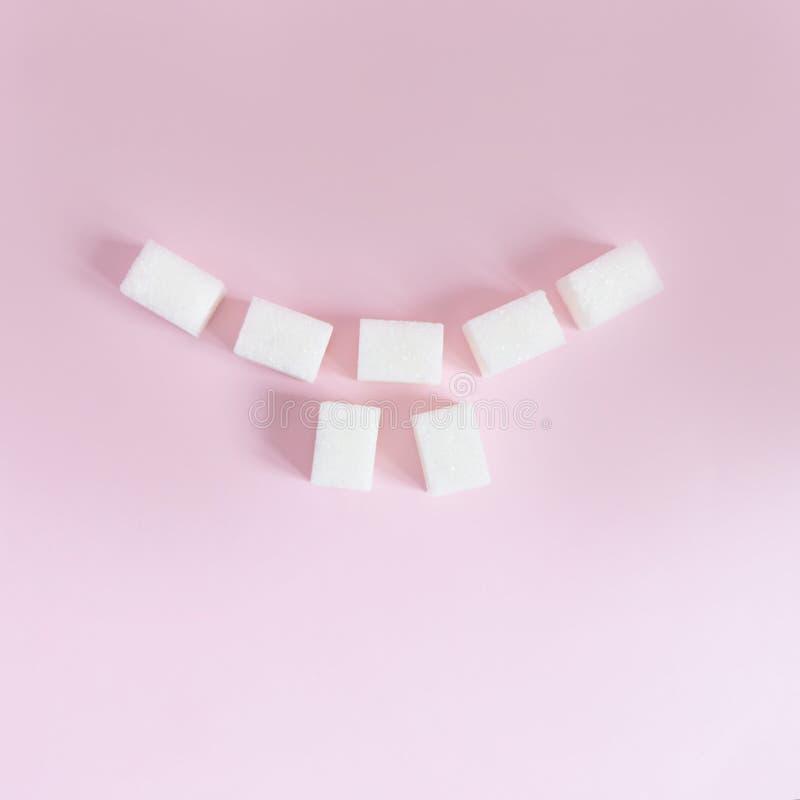 Los cubos del azúcar blanco se presentan bajo la forma de sonrisa con los dientes en un fondo rosado fotografía de archivo