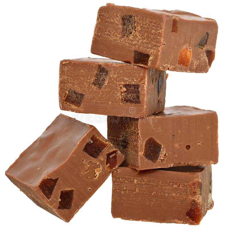 Los cubos del chocolate con leche llenaron de la fruta escarchada anaranjada aislada foto de archivo libre de regalías