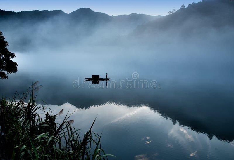 Los cucoloris de un fishman en el barco en la niebla en el río, una reflexión clara en el río tranquilo Tono fr?o fotografía de archivo