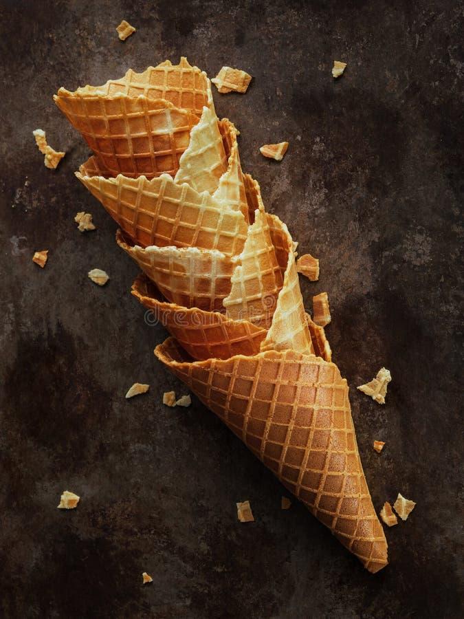 Los cucuruchos o el helado vacíos apilados hechos en casa se enrollan los conos en fondo oscuro fotos de archivo
