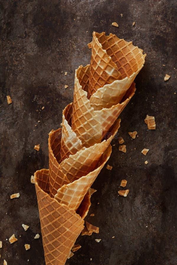 Los cucuruchos o el helado vacíos apilados hechos en casa se enrollan los conos en fondo oscuro foto de archivo libre de regalías