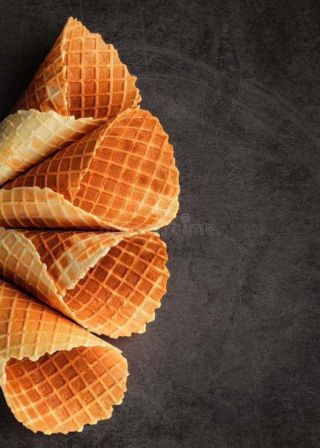 Los cucuruchos o el helado vacíos apilados hechos en casa se enrollan los conos en fondo oscuro foto de archivo