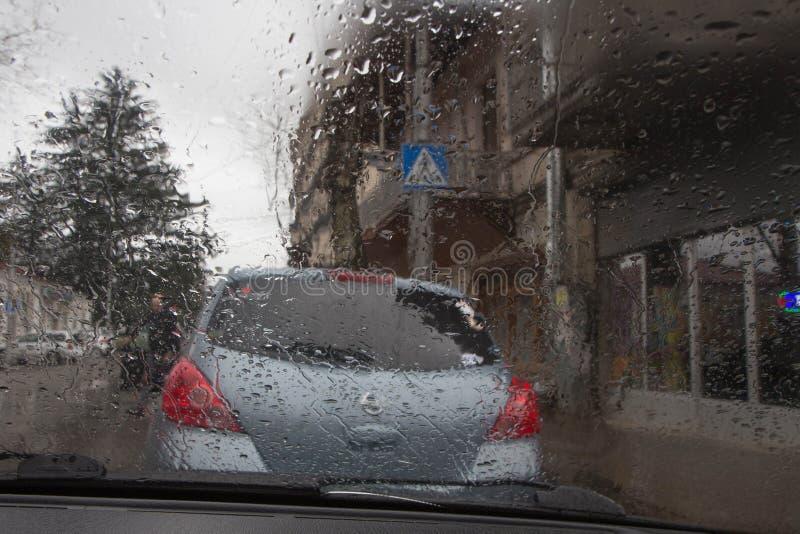 Los días lluviosos, tarde, lluvia caen en la ventana con la falta de definición del tráfico Silueta borrosa del coche foto de archivo libre de regalías