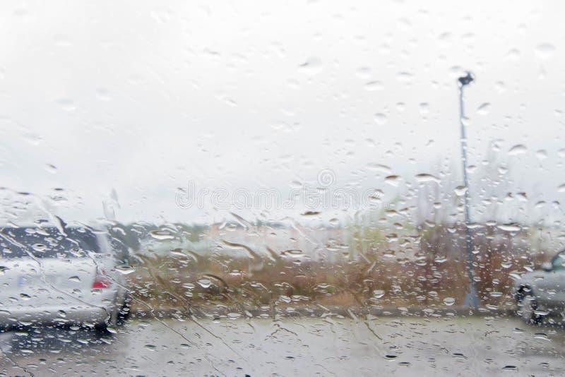 Los días lluviosos, tarde, lluvia caen en la ventana con la falta de definición del tráfico Silueta borrosa del coche imagen de archivo