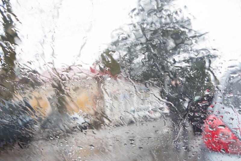 Los días lluviosos, tarde, lluvia caen en la ventana con la falta de definición del tráfico Silueta borrosa del coche imágenes de archivo libres de regalías
