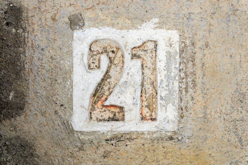 Los dígitos 21 con hormigón en la acera fotos de archivo