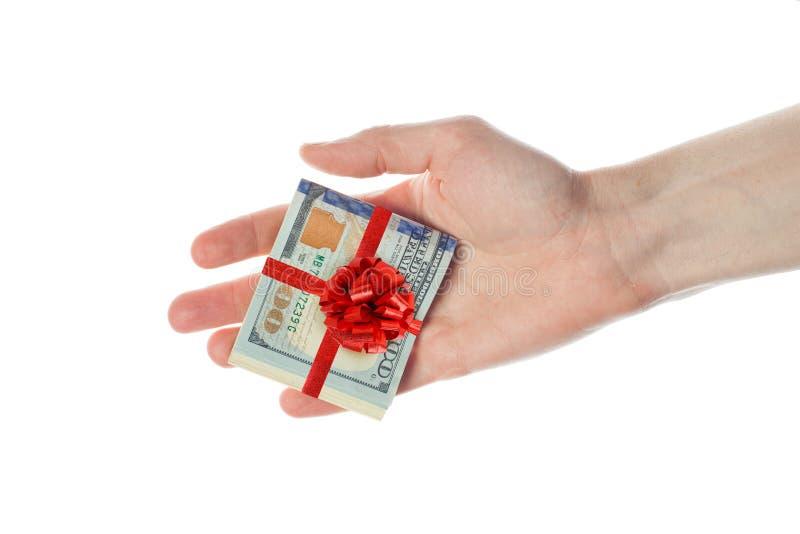 Los dólares americanos cobran con la cinta roja en la mano masculina aislada en el fondo blanco Regalo del billete de banco ameri imagenes de archivo