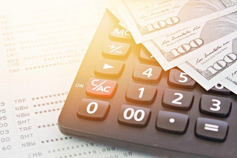 Los dólares americanos cobran el dinero, la calculadora en libreta de banco del cuenta de ahorros o el estado financiero fotografía de archivo libre de regalías