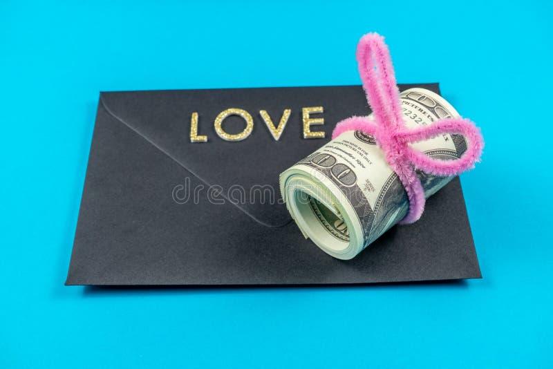Los dólares americanos rodaron para arriba y apretaron con la banda coloreada en fondo azul claro El negro sellado envuelve Amor fotografía de archivo libre de regalías