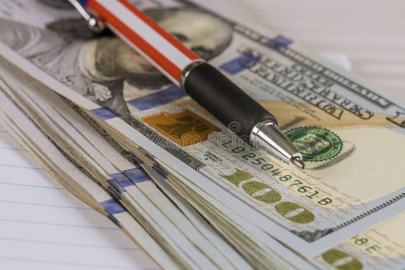 Los dólares cientos cuentas cobran el dinero con una pluma fotos de archivo