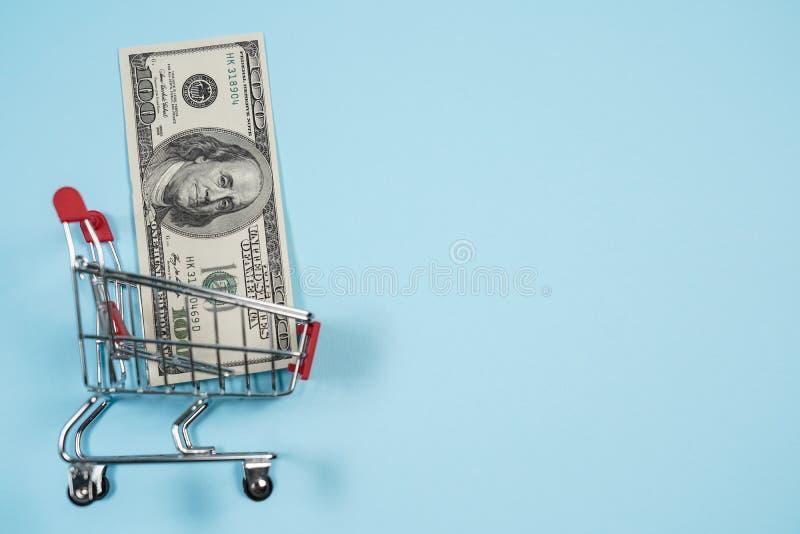 Los dólares de EE. UU. en carro de la compra sobre el fondo azul, billete de dólar recogen en el carro de la compra Concepto de d imagen de archivo libre de regalías