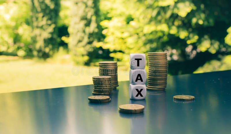 Los dados forman la palabra 'impuesto ' fotografía de archivo