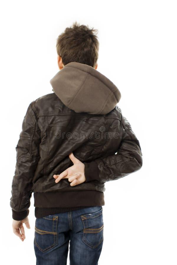 Los dedos de la travesía del muchacho detrás mueven hacia atrás fotografía de archivo libre de regalías