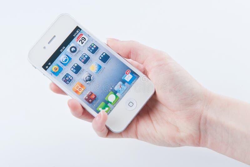 Los dedos de las mujeres guardan el iphone blanco 4 imagen de archivo