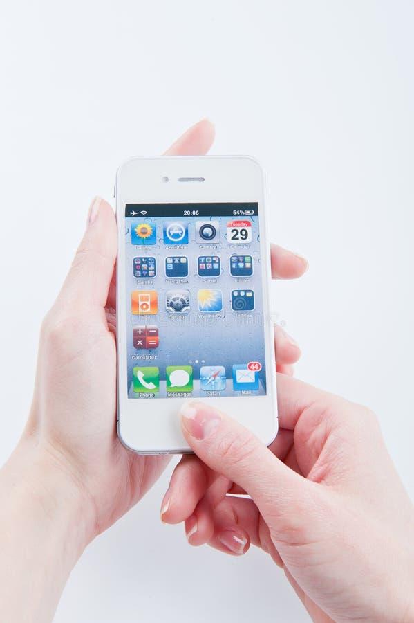 Los dedos de las mujeres guardan el iphone blanco 4 imagen de archivo libre de regalías