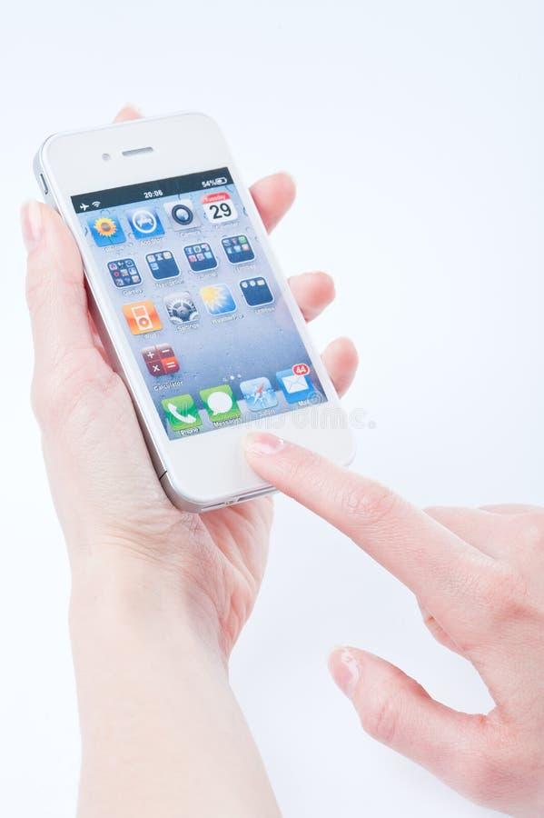 Los dedos de las mujeres guardan el iphone blanco 4 foto de archivo