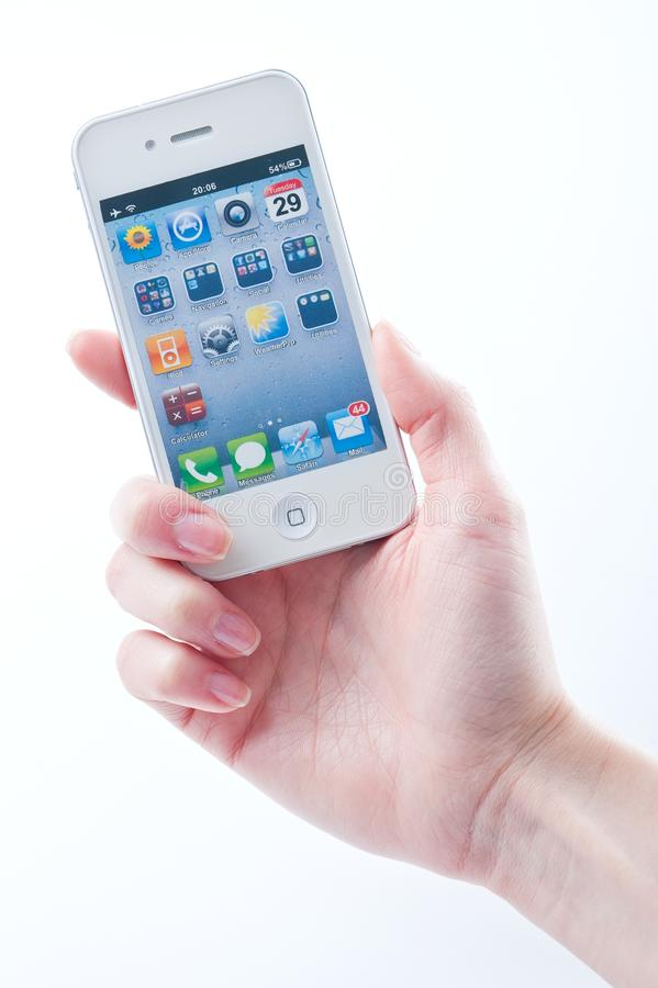 Los dedos de las mujeres guardan el iphone blanco 4 foto de archivo libre de regalías