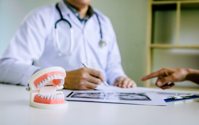 Los dentistas están discutiendo problemas dentales en la imagen de la radiografía del informe para los pacientes foto de archivo