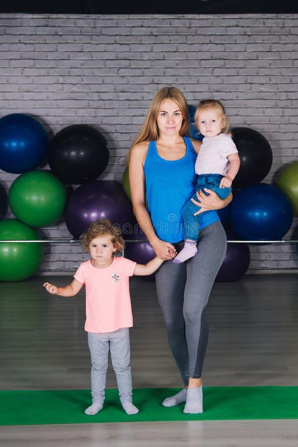 Los deportes mamá y bebés de los jóvenes hacen ejercicios juntos en el gimnasio foto de archivo libre de regalías