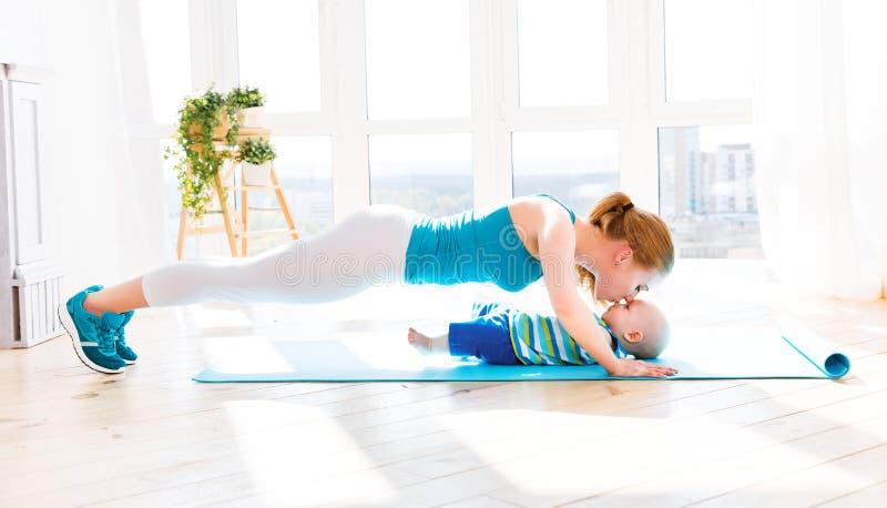 Los deportes miman se enganchan a aptitud y a yoga con el bebé en casa imagenes de archivo